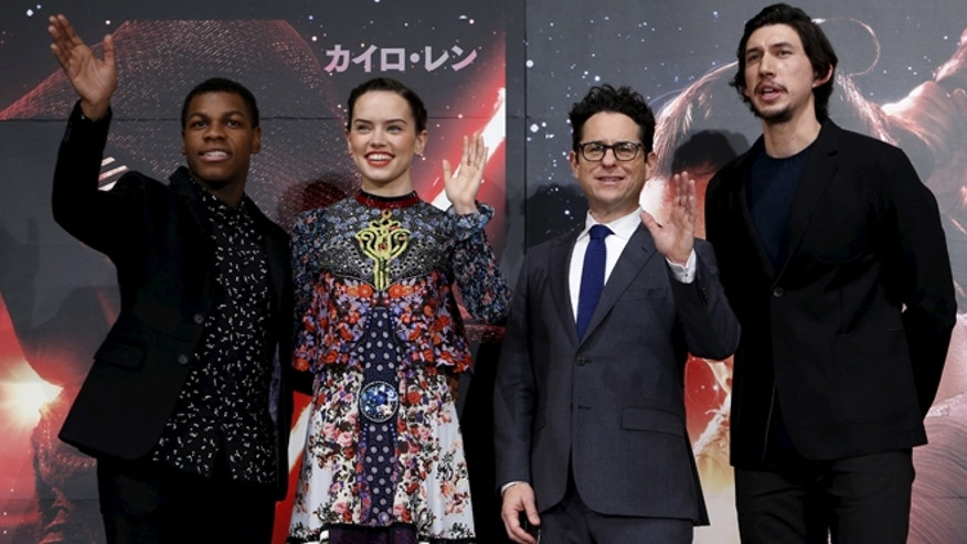 "December 11, 2015. Director J.J. Abrams (2nd R), cast members John Boyega (L), Daisy Ridley (2nd L), and Adam Driver pose for pictures with ""Star Wars"" character BB-8 8(C) in Tokyo."