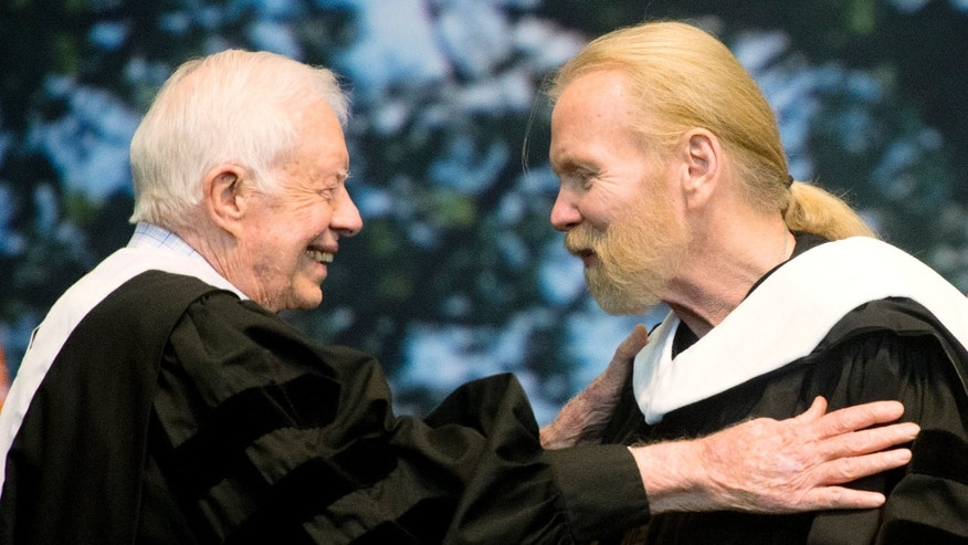 Jimmy Carter hugs Gregg Allman who received an honorary degree at Mercer University in Macon, Ga.