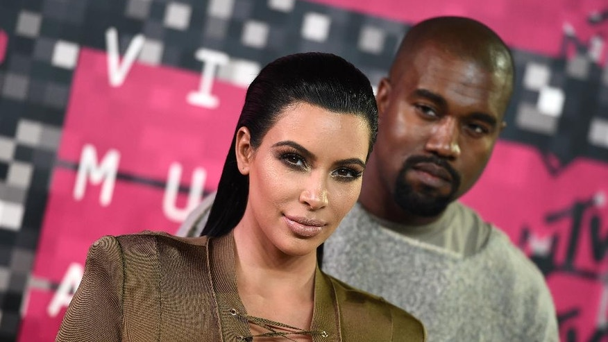 "FILE - In this Aug. 30, 2015, file photo, Kim Kardashian, left, and Kanye West arrive at the MTV Video Music Awards at the Microsoft Theater in Los Angeles. Kardashian praised her husband's May 19, 2016, appearance on ""The Ellen DeGeneres Show"" on Twitter. (Photo by Jordan Strauss/Invision/AP, File)"