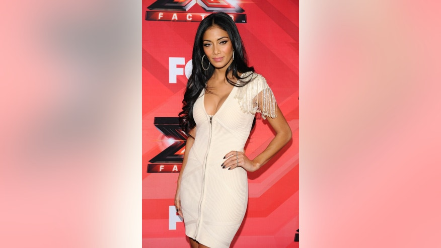 "Judge Nicole Scherzinger poses for photographers following a news conference for the television show ""The X Factor"" held in Los Angeles December 19, 2011. REUTERS/Phil McCarten (UNITED STATES - Tags: ENTERTAINMENT) - RTR2VGPO"