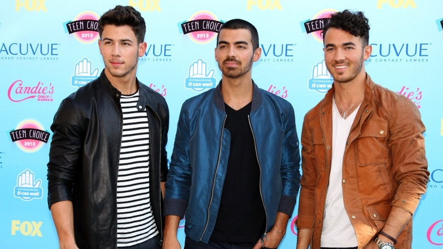 Singers (L-R) Nick, Joe and Kevin Jonas pose as they arrive at the Teen Choice Awards at the Gibson amphitheater in Universal City, California August 11, 2013.