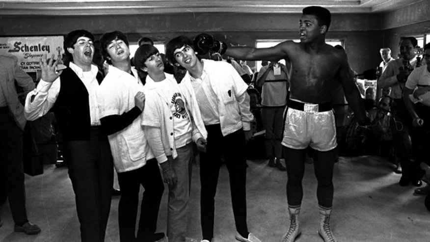 Feb. 18, 1964, take a fake blow from Cassius Clay (Muhammad Ali) while visiting the heavyweight contender at his training camp in Miami Beach, Fla