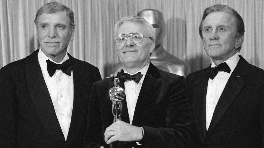 "In this file photo dated March 25, 1985, actors Burt Lancaster, left, and Kirk Douglas, right, stand with Peter Shaffer, winner of the best adapted screenplay Oscar for ""Amadeus"", during the Academy Awards in Los Angeles, Ca., USA, March 25, 1985."