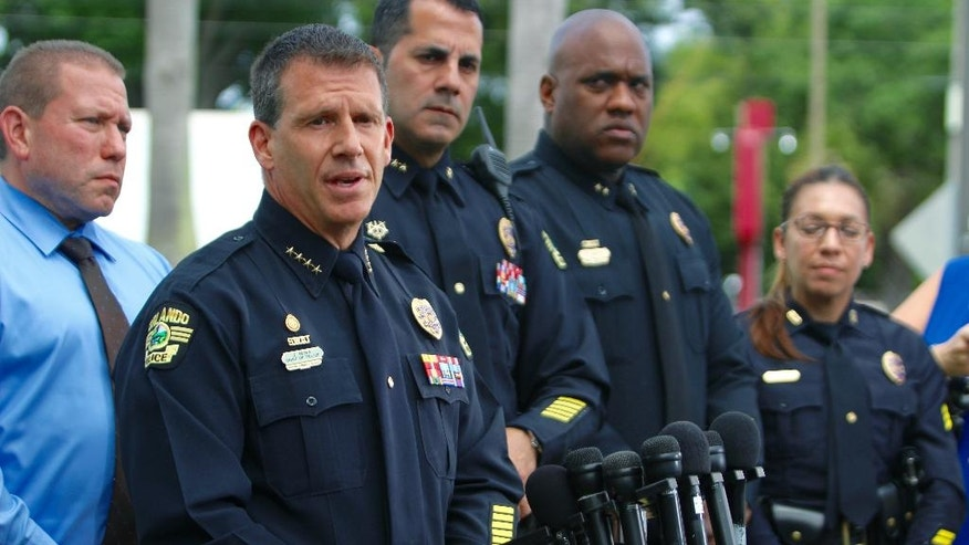"""Orlando Police Chief John Mina, second from left,  holds a press conference Saturday, June 11, 2016, in Orlando, Fla., outside The Plaza Live theater, the location where singer Christina Grimmie was shot and killed the night before. The gunman who shot and killed the singer who rose to fame after appearing on """"The Voice"""" traveled to Orlando from another Florida city specifically to attack her and then fatally shot himself, authorities said Saturday.  (Jordan Krumbine/Orlando Sentinel via AP) MAGS OUT; NO SALES; MANDATORY CREDIT"""