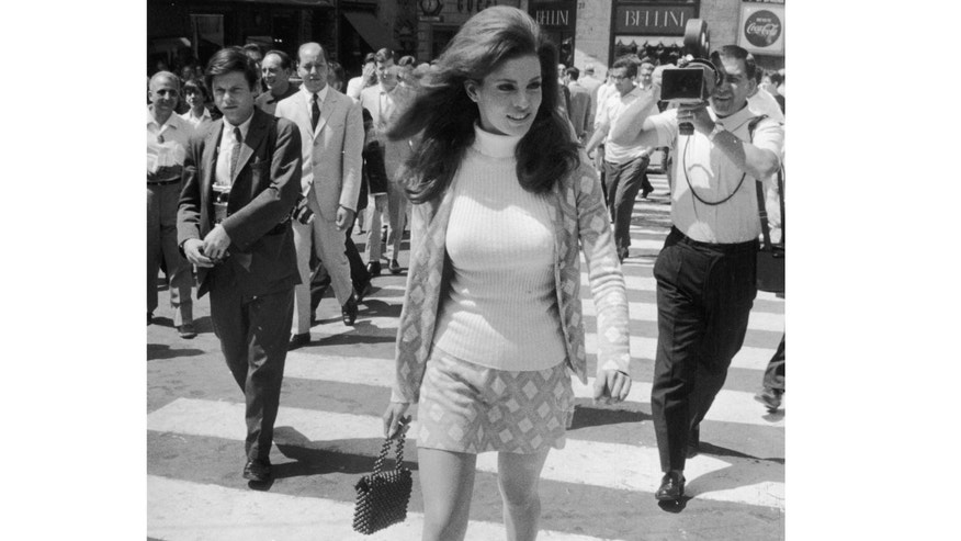 Raquel Welch strides across a zebra crossing in Spanish Square, Rome followed by photographers.
