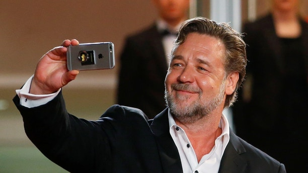 "Cast member Russell Crowe uses a smartphone while arriving on the red carpet for the screening of the film ""The Nice Guys"" out of competition at the 69th Cannes Film Festival in Cannes, France, May 15, 2016.    REUTERS/Yves Herman - RTSEFDK"