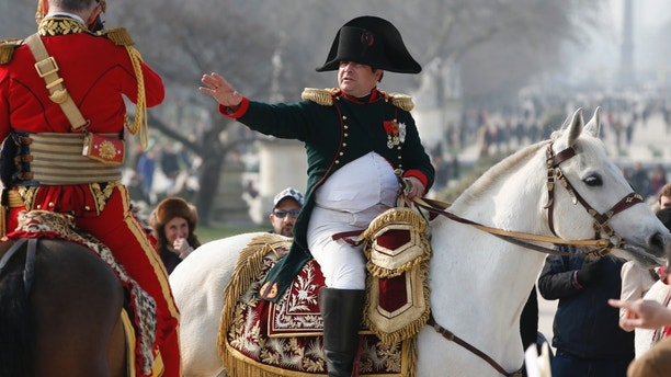 Frenchman Frank Samson takes part in an re-enactment as French Emperor Napoleon who rides on horseback in the Tuileries Gardens upon his return to Paris, as part of the Bicentennial, in Paris March 20, 2015.  This year marks the bicentennial of the return of Napoleon Bonaparte to France after nine months of exile on the Island of Elba.     REUTERS/Charles Platiau - RTR4U7KG