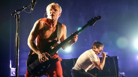 FILE - In this Feb. 5, 2016, file photo, Flea, left, and Anthony Kiedis of the Red Hot Chili Peppers perform at The Theatre at Ace Hotel in Los Angeles. Flea wrote on Instagram July 10, 2016, that his band was mistaken for Metallica at an airport in Belarus and was forced to autograph Metallica items. (Photo by Rich Fury/Invision/AP, File)