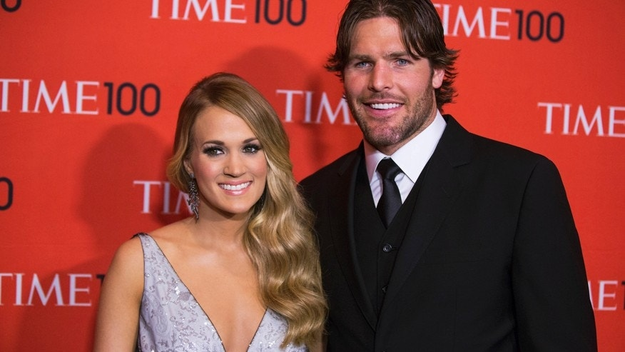 Honoree and singer Carrie Underwood arrives with her husband Mike Fisher at the Time 100 gala celebrating the magazine's naming of the 100 most influential people in the world for the past year, in New York April 29, 2014.