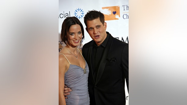 Actress Emily Blunt (L) and boyfriend and singer Michael Buble arrive at the 11th annual Andre Agassi Charitable Foundation's Grand Slam benefit concert at the MGM Grand Garden Arena in Las Vegas, Nevada October 7, 2006. Picture taken October 7, 2006. REUTERS/Tiffany Brown  (UNITED STATES) - RTR1I4V3