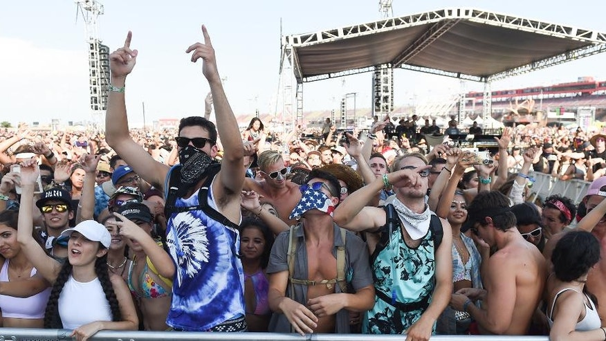 In this Sunday, July 31, 2016, photo, people attend the HARD Summer Music Festival at the Auto Club Speedway in Fontana, Calif. Authorities say multiple people died after attending the weekend rave. (John Valenzuela/The Sun via AP)