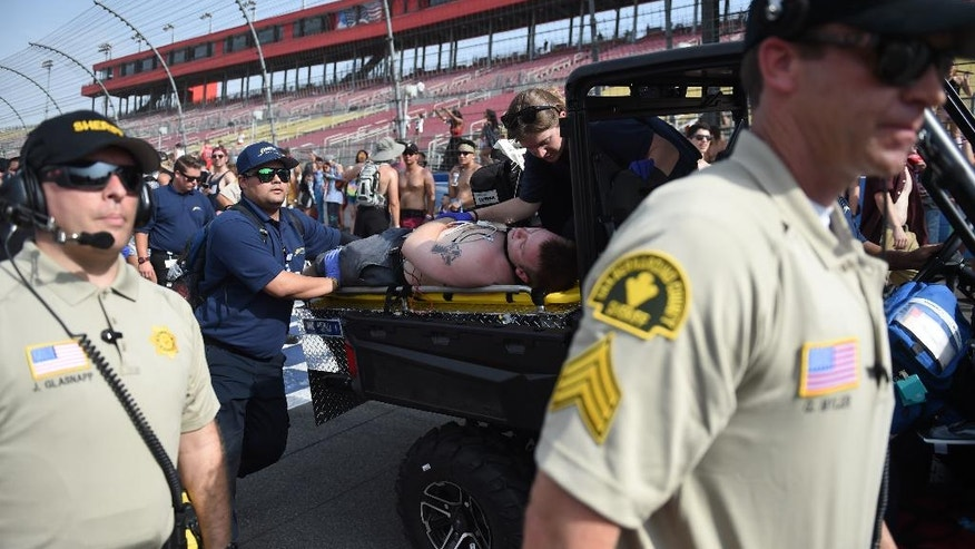 In this July 30, 2016, photo, rescue personnel carry a man off the concert grounds on a stretcher, for an unspecified reasons, at HARD Summer Music Festival at the Auto Club Speedway in Fontana, Calif. Authorities say multiple people died after attending the weekend rave. (John Valenzuela/The Sun via AP)