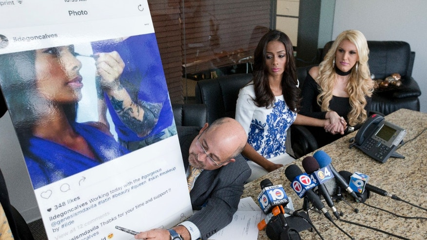 Attorney Richard Wolfe, points to a photo and posting on social media by Genesis Davila, center, Miss Florida USA 2017 who's crown was recently taken away, as she holds hands with her coach and life mentor Jenny Patrizia, during a news conference, Monday, Aug. 1, 2016, in Miami.