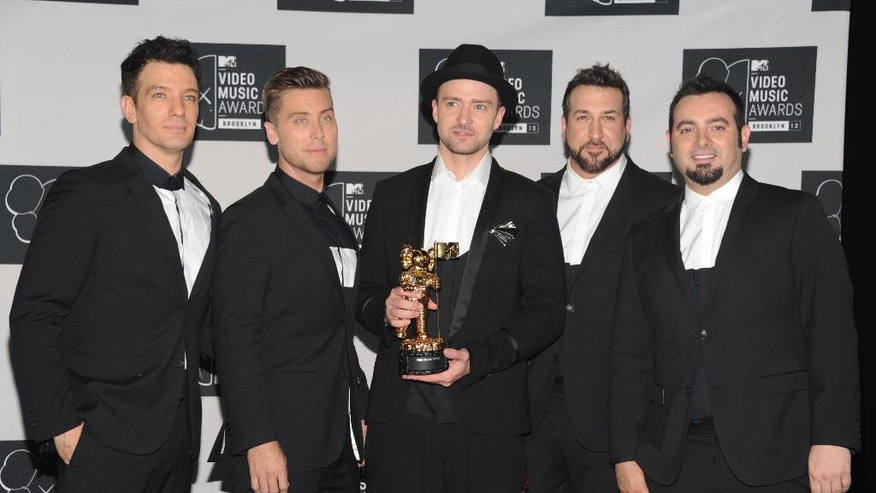 FILE - In this Aug. 25, 2013, file photo, Justin Timberlake, center, winner of the video vanguard award poses backstage with, from left, JC Chasez, Lance Bass, Joey Fatone and Chris Kirkpatrick of NSYNC at the MTV Video Music Awards at the Barclays Center in New York. Timberland and the band's Twitter account posted a picture of the group celebrating Chasez's 40th birthday party on Aug. 9, 2016. (Photo by Evan Agostini/Invision/AP, File)