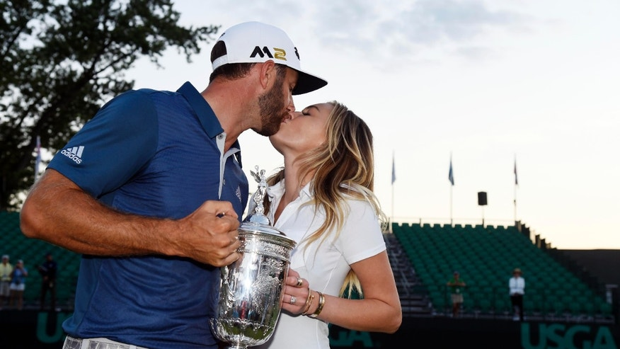 Jun 19, 2016; Oakmont, PA, USA; Dustin Johnson kisses his fiance Paulina Gretzky while holding the championship trophy after winning the U.S. Open golf tournament at Oakmont Country Club.