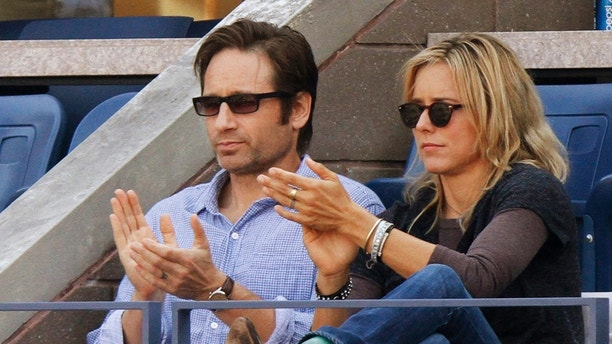 Actors David Duchovny and Tea Leoni applaud during the match between Rafael Nadal of Spain and Novak Djokovic of Serbia during the men's final at the U.S. Open tennis tournament in New York September 13, 2010.  REUTERS/Eduardo Munoz (UNITED STATES - Tags: SPORT TENNIS ENTERTAINMENT) - RTR2IAR4