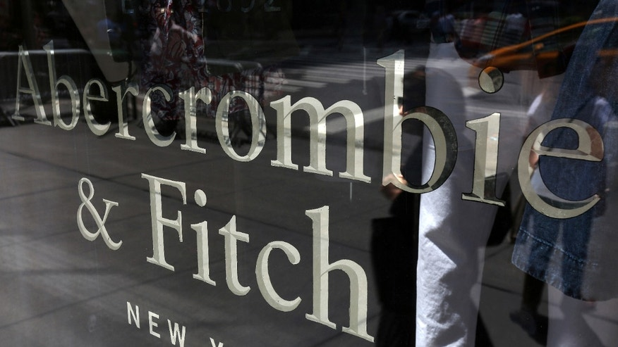 A woman is reflected in a window as she walks past an Abercrombie & Fitch store on 5th Avenue in the Manhattan borough of New York.
