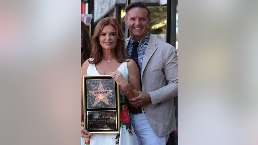 Roma Downey poses with husband Mark Burnett  as she receives her star on the Hollywood Walk of Fame in Hollywood, California on August 11, 2016. ..(Photo: Alex J. Berliner/ABImages)