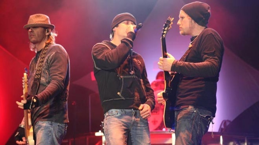 Matt Roberts (r.) performs with 3 Doors Down bandmates Todd Harrell (l.) and Brad Arnold in 2011.