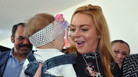 U.S. actress Lindsay Lohan holds a Syrian refugee child as she visits a Turkish government-run Syrian refugee camp in Nizip near Turkey's border with Syria, Saturday, Oct. 8, 2016. The Anadolu Agency said Saturday the U.S. actress toured the social facilities and preschool in Nizip before giving refugee children there presents. (AP Photo)