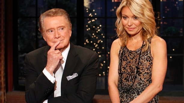 "Television host Regis Philbin says goodbye with co-host Kelly Ripa (R) during his final show of on  ""Live With Regis and Kelly"" in New York, November 18, 2011.  After nearly three decades hosting the show that became ""Live With Regis and Kelly,"" Regis Philbin stepped down Friday with a few well wishes to his colleagues and fans.  REUTERS/Brendan McDermid (UNITED STATES - Tags: ENTERTAINMENT PROFILE) - RTR2U6IY"