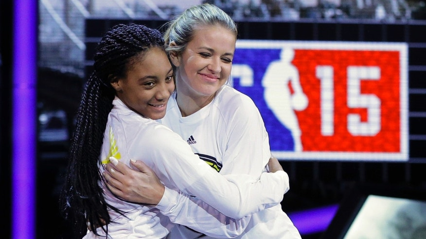 "FILE - In this Feb. 13, 2015, file photo, Kristen Ledlow, right, hugs Mo'ne Davis as they are announced before the NBA All-Star celebrity basketball game in New York. Ledlow said on social media Oct. 23, 2016, that she was robbed at gunpoint. Ledlow is the host of ""NBA Inside Stuff"" on NBA TV. (AP Photo/Frank Franklin II, File)"