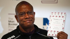 "Writer Paul Beatty poses for the media with his book ""The Sellout"" during a photocall for the 6 shortlisted authors for the Man Booker Prize for fiction in London, Monday, Oct. 24, 2016. This will be the third year the £50,000 (61,000 US$), prize has been open to any writer, writing originally in English and published in the UK, irrespective of nationality.(AP Photo/Alastair Grant)"