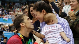 FILE - In this Aug. 9, 2016, file photo, United States' swimmer Michael Phelps celebrates winning his gold medal in the men's 200-meter butterfly with his fiance Nicole Johnson and baby Boomer during the swimming competitions at the 2016 Summer Olympics, in Rio de Janeiro, Brazil. The Arizona Republic reported Oct. 26, 2016, that Phelps and Johnson secretly married on June 13, 2016. (AP Photo/Matt Slocum, File)