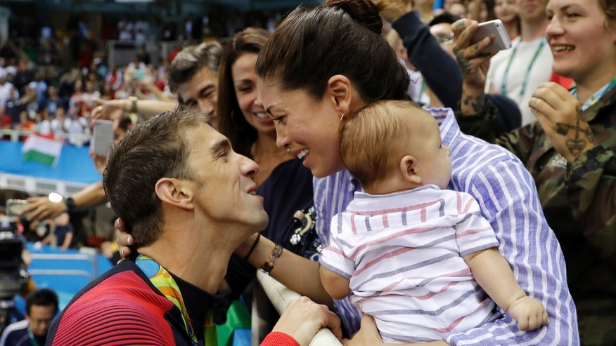 In this Aug. 9, 2016, file photo, United States' swimmer Michael Phelps celebrates winning his gold medal in the men's 200-meter butterfly with his fiance Nicole Johnson and baby Boomer during the swimming competitions at the 2016 Summer Olympics, in Rio de Janeiro, Brazil.