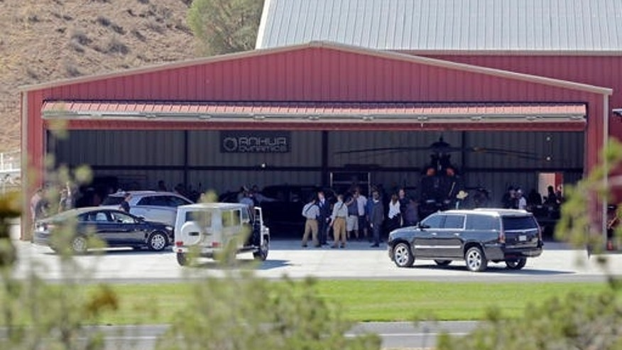 FILE - In this Wednesday, July 6, 2016 file photo, members of a film crew stand at Agua Dulce Airpark, a small, rural airport in Agua Dulce, Calif., in northern Los Angeles County. Steve de Castro, a stuntman who was injured in when he was run over by Tom Sizemore while filming the upcoming television series âShooterâ at the site on July 6 has sued the actor and Paramount Pictures over the accident in Los Angeles Superior Court on Friday, Oct. 28, 2016, stating the accident was preventable and left him with lasting injuries that have hampered his ability to work. (AP Photo/Reed Saxon)
