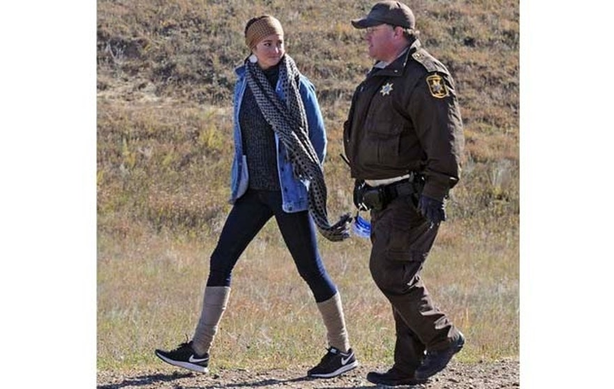 FILE - In this Oct. 10, 2016. file photo, actress Shailene Woodley, left, is led to a transport vehicle by a Morton County Sheriff's deputy after being arrested at a protest against the Dakota Access Pipeline near St. Anthony, N.D. Woodley is to stand trial in North Dakota in early 2017 on charges related to her protest. (Tom Stromme/The Bismarck Tribune via AP, File)