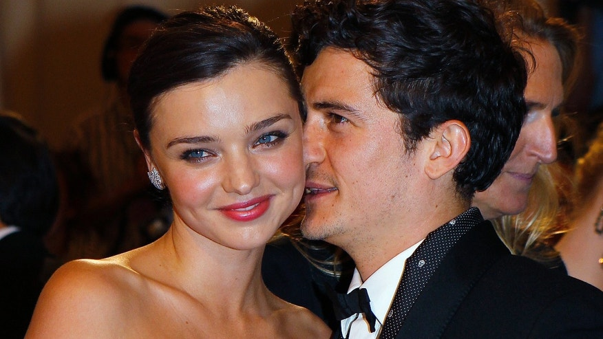 Miranda Kerr and Orlando Bloom pose on the red carpet at the Metropolitan Museum of Art Costume Institute Benefit celebrating the opening of Alexander McQueen: Savage Beauty, in New York, May 2, 2011.