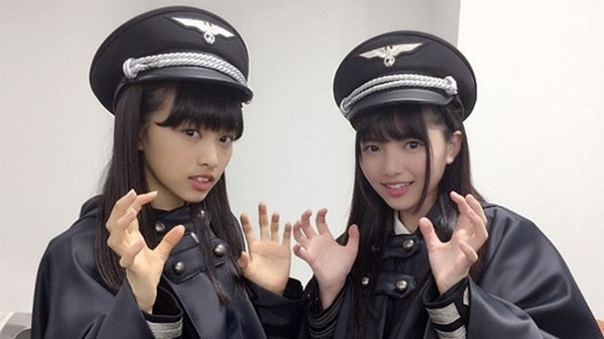 Two girls from the Japanese music group Keyakizaka46 pose for a picture wearing the outfits many called out for resembling Nazi-era German military uniforms.