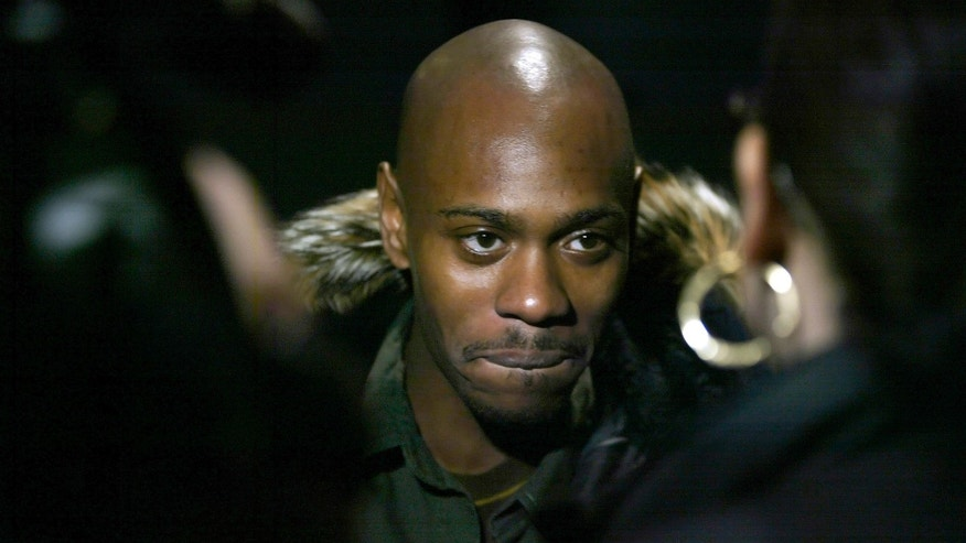 Comedian Dave Chappelle talks to reporters as he arrives for the premiere of his film 'Dave Chappelle's Block Party' in New York February 28, 2006. REUTERS/Keith Bedford - RTR16QS5