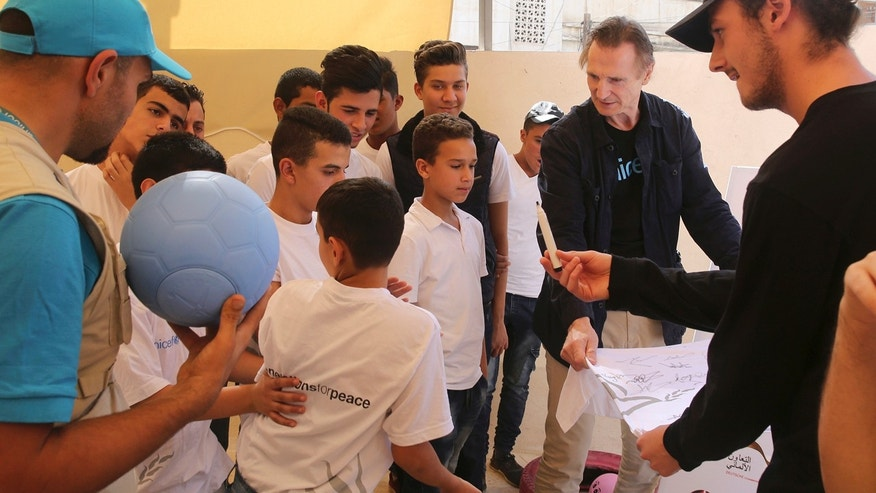In this Tuesday, Nov. 8, 2016 photo, actor Liam Neeson, holds a shirt for Syrian and Jordanian students to sign for him at a community center in a working-class neighborhood of Amman, Jordan.