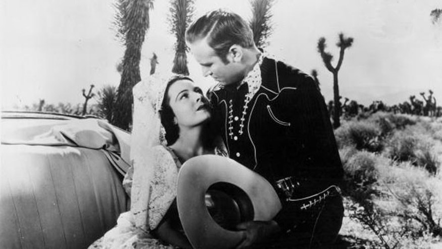 1939:  Actor Gene Autry contemplates sultry Lupita Tovar in the Republic Pictures western 'South of the Border'.  (Photo by Hulton Archive/Getty Images)