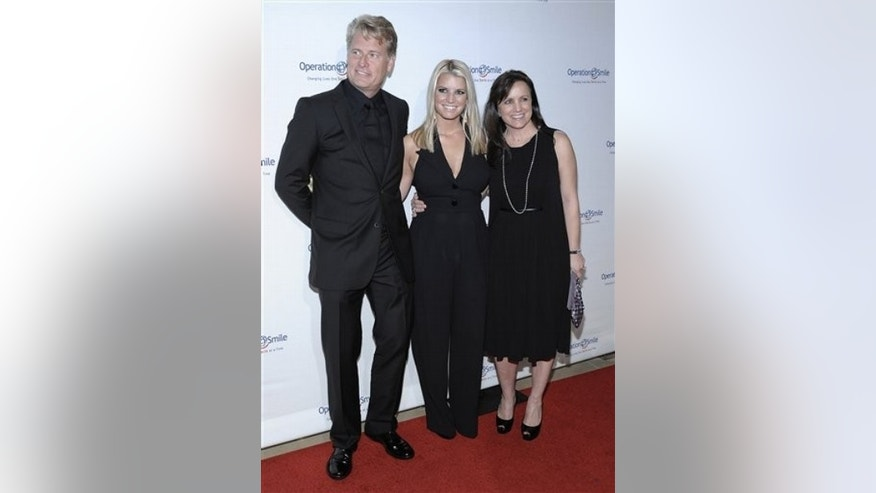 "Singer Jessica Simpson, center, her father Joe Simpson, right, and mother Tina Simpson arrive at the Operation Smile ""Smile Gala"" in Beverly Hills, Calif. on Friday, Oct. 2, 2009. (AP Photo/Dan Steinberg)"
