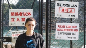 "In this photo released by DolphinProject, Maisie Williams stands in front of a fence with notice boards beside the beach known for dolphin hunting in Taiji, Wakayama prefecture, central Japan, Friday, Dec. 2, 2016. ""Game of Thrones"" star Williams, 19, wants everyone to stop buying tickets to marine shows, the best way, she thinks, to stop the dolphin capture and killing in Japan. Williams spoke Friday from the small Japanese town of Taiji, made famous in ""The Cove"" an Oscar-winning film that documented the dolphin hunt and starred Ric O'Barry, the dolphin trainer for the ""Flipper"" TV series. (Lincoln O'Barry via AP)"
