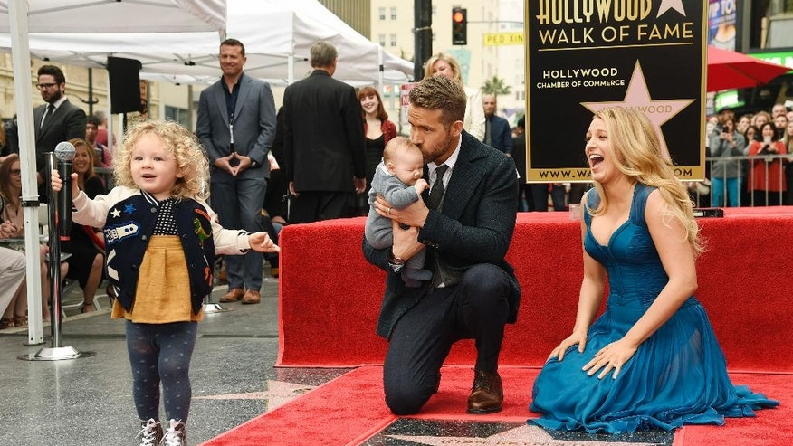 Ryan Reynolds' daughter James, left, steals the microphone as Reynolds poses with his wife, actress Blake Lively, and their youngest daughter during a ceremony to award him a star on the Hollywood Walk of Fame on Thursday, Dec. 15, 2016, in Los Angeles (Photo by Chris Pizzello/Invision/AP)
