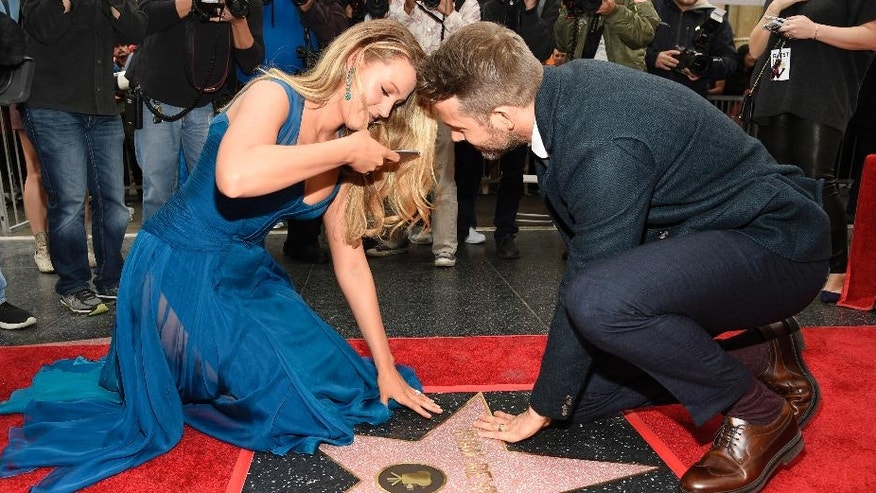 Actor Ryan Reynolds, right, joins his wife, actress Blake Lively, as she photographs his new star on the Hollywood Walk of Fame following a ceremony on Thursday, Dec. 15, 2016, in Los Angeles. (Photo by Chris Pizzello/Invision/AP)