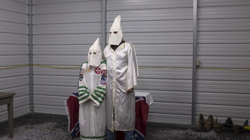 A female and male member of the Virgil Griffin White Knights, a group that claims affiliation with the Ku Klux Klan, pose for a photograph in their robes ahead of a cross lighting ceremony at a private farm house in Carter County, Tennessee July 4, 2015.