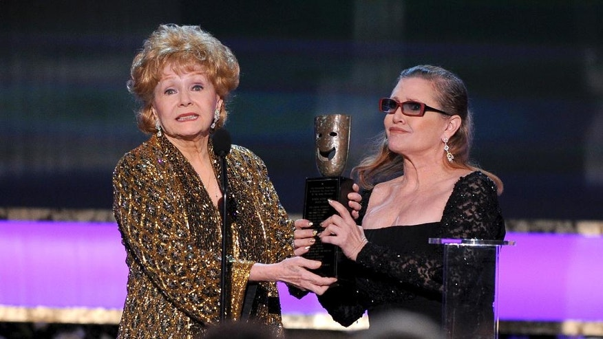 "FILE- In this Jan. 25, 2015, file photo, Carrie Fisher, right, presents her mother Debbie Reynolds with the Screen Actors Guild life achievement award at the 21st annual Screen Actors Guild Awards at the Shrine Auditorium in Los Angeles. ""La La Land"" star Ryan Gosling thanked Reynolds at the Palm Springs Film Festival on Monday, Jan. 2, 2017, for serving as an inspiration to the cast and crew of the film. (Photo by Vince Bucci/Invision/AP, File)"