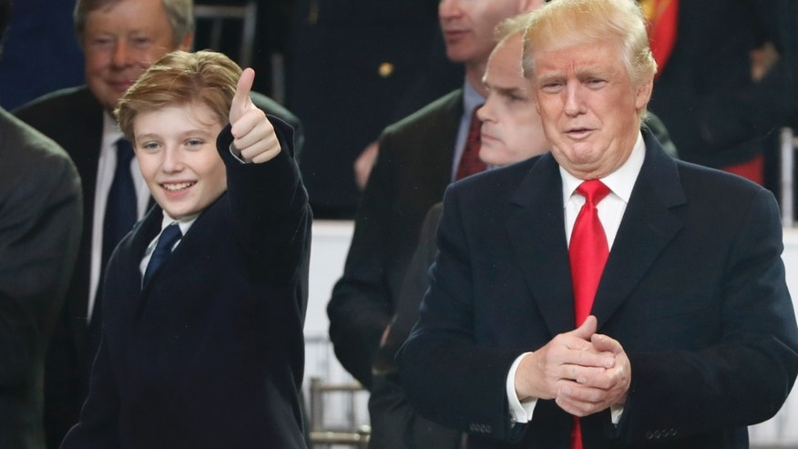 President Donald Trump, right, and his son Barron react as they view the 58th Presidential Inauguration parade for Donald Trump in Washington. Friday, Jan. 20, 2017.