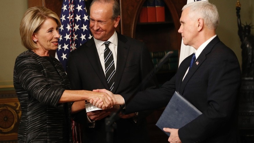 Vice President Mike Pence shakes hands after swearing in Education Secretary Betsy DeVos in the Eisenhower Executive Office Building in the White House complex in Washington, Tuesday, Feb. 7, 2016, as DeVos' husband Dick DeVos watches.