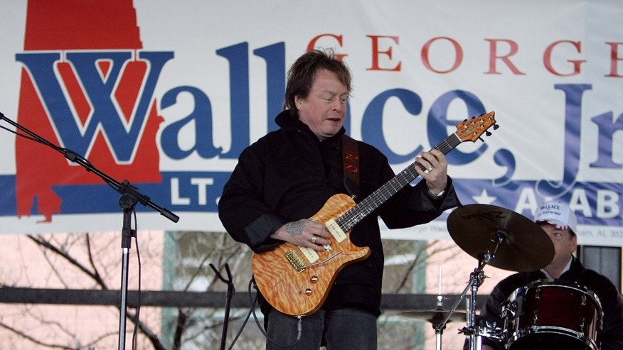 In this Feb. 18, 2006 file photo, Rick Derringer performs during a campaign rally kicking off George Wallace Jr's bid for the office of lieutenant governor in Montgomery, Ala.  Prosecutors say  Derringer carried a loaded gun in his carry-on bag on a Delta Air Lines flight from Cancun, Mexico, but was stopped after landing in Atlanta.
