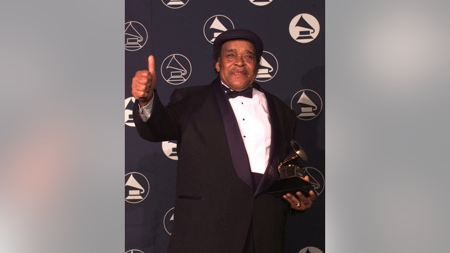 "In this Feb. 26, 1997 file photo, blues musician James Cotton holds up a thumbs-up sign after winning the Best Traditional Blues Album during the pre-telecast program of the 39th Annual Grammy Awards in New York. Cotton won for his work ""Deep In The Blues."" Cotton, a Grammy Award-winning blues harmonica master whose full-throated sound backed such blues legends as Muddy Waters, Sonny Boy Williamson II and Howlin' Wolf, has died at age 81."