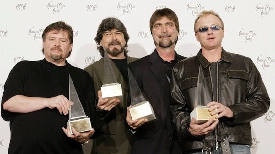 "Members of the country band ""Alabama"" pose with their Award of Merit at