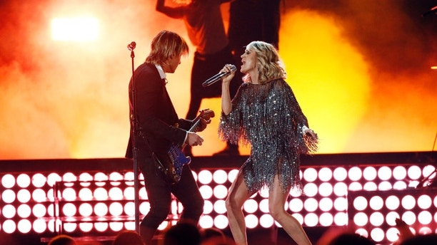 """Keith Urban (left) and Carrie Underwood perform """"The Fighter"""" at the 52nd Academy of Country Music Awards in Las Vegas, Nevada on April 2, 2017."""