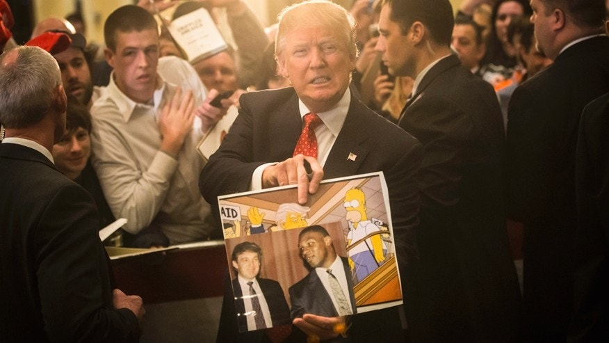 "In this Jan. 29, 2016, file photo, Republican presidential candidate Donald Trump holds depictions of himself on, ""The Simpsons"" and a photo with boxer Mike Tyson, given to him by an attendee during a campaign stop at the Radisson Hotel in Nashua, N.H. ""The Simpsons"" released a short online clip on April 26, 2017, mocking President Donald Trump ahead of his 100th day in office."