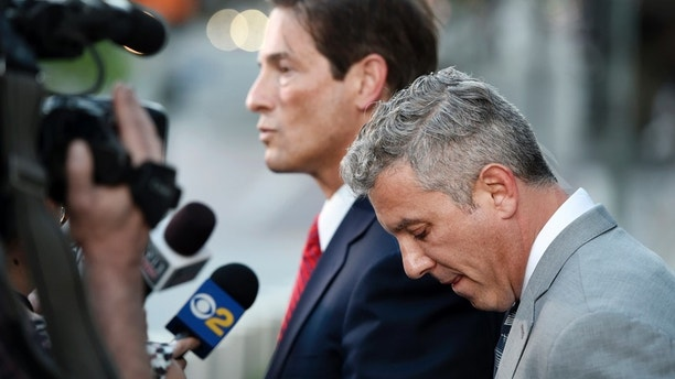 Jonathan Todd Schwartz, right, former business manager for singer Alanis Morissette, looks down as his attorney Nathan Hoffman addresses reporters outside U.S. federal court following sentencing in his embezzlement case, Wednesday, May 3, 2017, in Los Angeles. Schwartz was sentenced to six years in federal prison for stealing more than $7 million from the singer and other clients, and was ordered to pay $8.6 million in restitution.